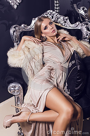 Sexy woman in beige silk dress sitting on the black armchair