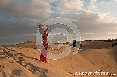 Sexy woman belly dancer arabian in desert dunes