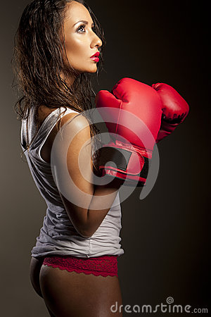 Sexy woman boxer pausing during training