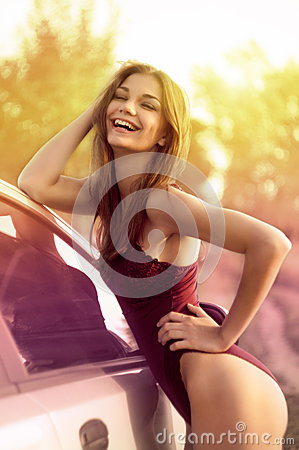 Sexy woman and car on green field