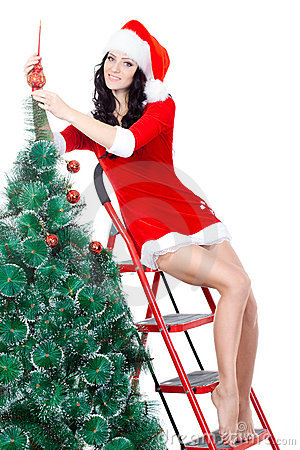 Sexy woman decorating the fur tree on stepladder