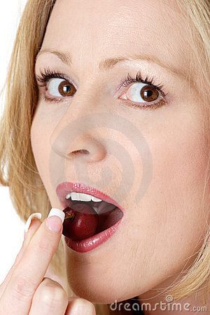 Sexy woman eating a cherry