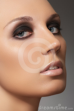 Sexy woman face with smoky eyes makeup, clean skin