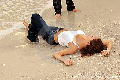 Sexy woman laying on beach in wet jeans