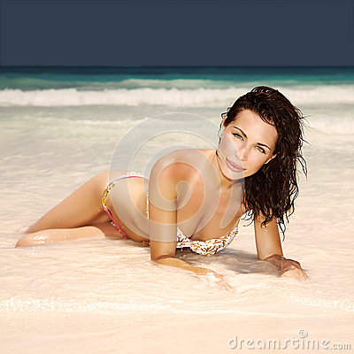 Sexy woman lying down on the beach