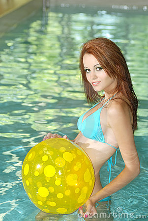 Sexy woman playing with yellow beach ball in pool