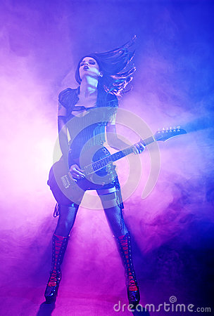 Sexy woman plays guitar at the concert