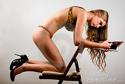 Sexy woman reading a magazine on chair indoors