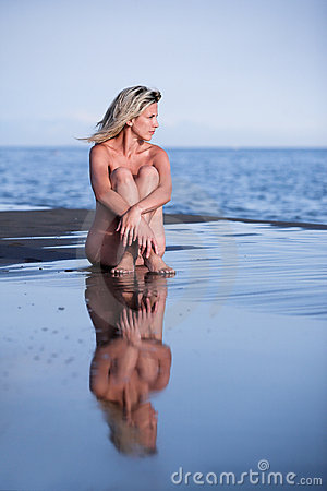 Sexy woman sits on wet sand at beach