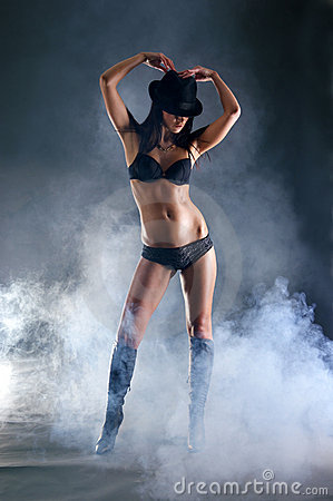A sexy woman standing in a hat an erotic lingerie