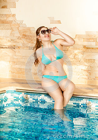 Sexy woman in sunglasses sitting at swimming pool