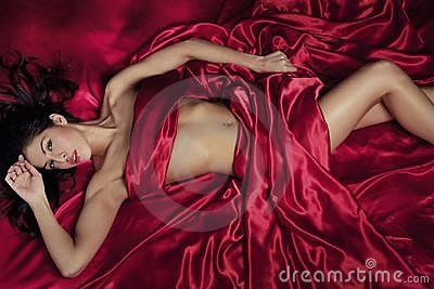 Sexy woman under satin sheets