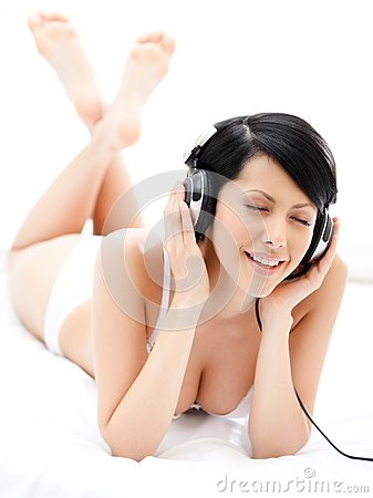 Sexy woman in underwear listens to music