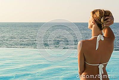 Sexy woman in white bikini looking far