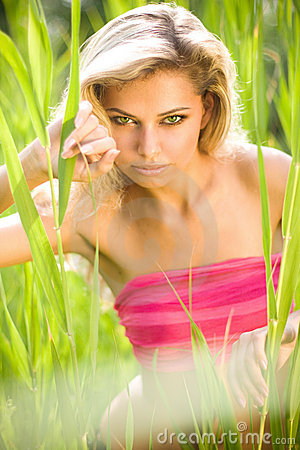 Sexy young blond woman in green grass