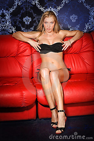 Sexy young blonde lady on red sofa
