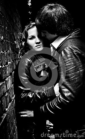Sexy young couple hugging and leaning against wall