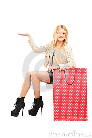 A sexy young female gesturing next to a shopping bag
