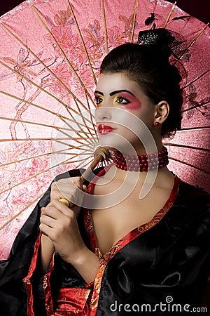 Sexy young geisha holding an umbrella