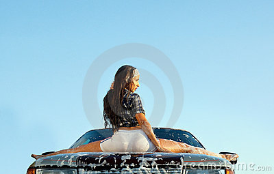 Sexy young girl sit on car in foam at sunset