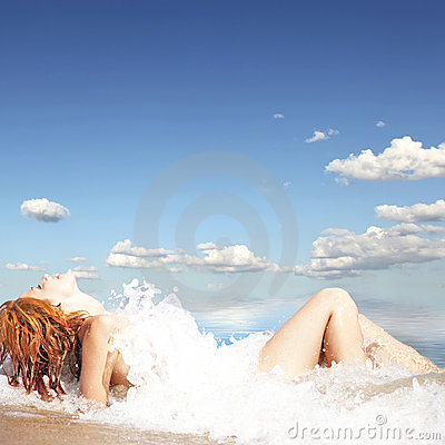 Sexy young red-haired girl on the beach.