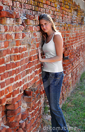 Sexy young woman against a brick wall