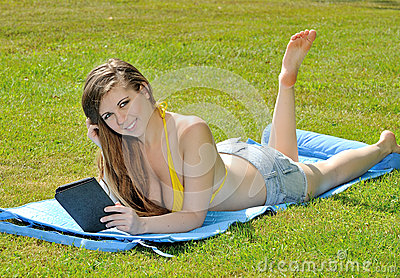 Sexy young woman in bikini top reading