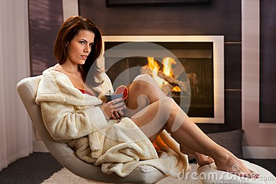 Sexy young woman having tea at home