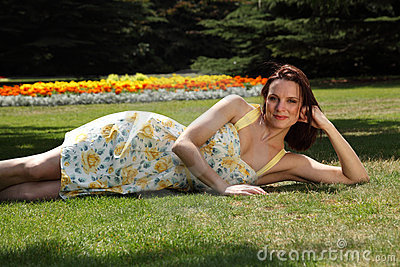 Sexy young woman lying on grass in summer sunshine