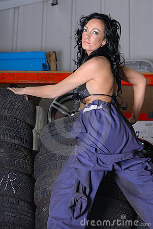 Sexy young woman posing on tyres