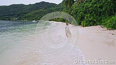 Seychelles El avión de drones sigue a una joven que corre a lo largo de la playa del paraíso con palmeras en la isla de Mahe Viaj almacen de metraje de vídeo