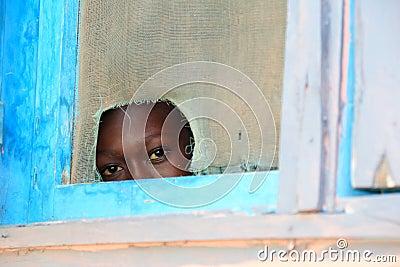 Sguardo inquisitore attraverso una finestra, Africa Fotografia Editoriale