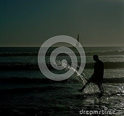 Shadow people beach kicking water