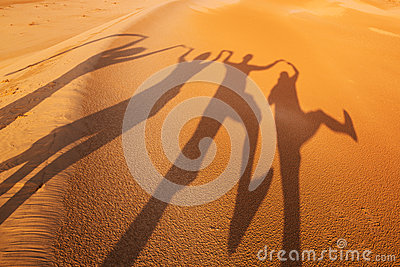 Shadow silhouettes of four people in the desert
