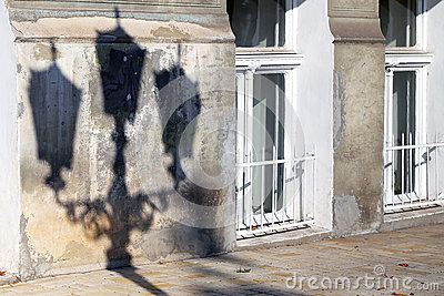 The shadow of a street lamp on the wall of an old dilapidated ho