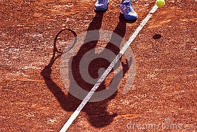 Shadow of a Tennis Player on a Clay Tennis Court