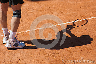 Shadow of a tennis player on court