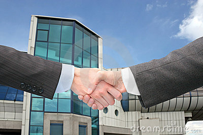 Shaking hands with wrists near blue building