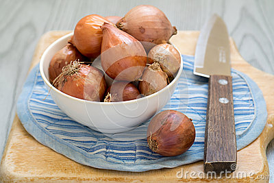 Shallots with knife on wooden cutting board