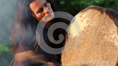 Shaman with a tambourine by the fire in the forest stock footage