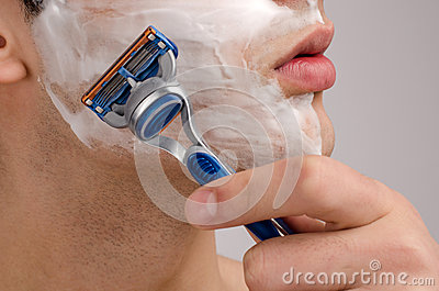 Shaving  the beard with a razor.
