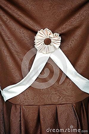 Sheath brown chair with a white ribbon