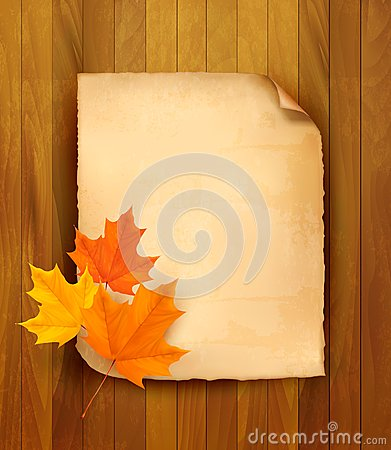 Sheet of paper with autumn leaves on wooden backgr