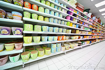 Shelves with variety of clay flowerpot inside shop