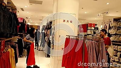 Shenzhen, Chine : Le paysage int?rieur du magasin de v?tement d'Uniqlo, femmes choisissent des v?tements clips vidéos