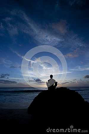 Shilouette of man meditating on the beach