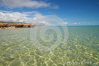 Shimmering ocean against blue sky