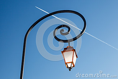 Shining Backlit Streetlamp and Airplane Trail