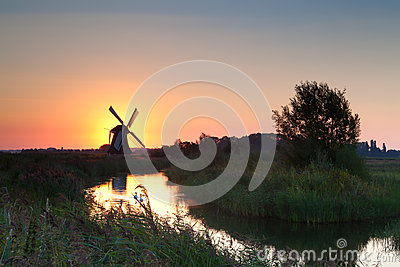 Shining windmill during sunrise over river