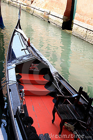Shiny black and red gondola in Venetian canal